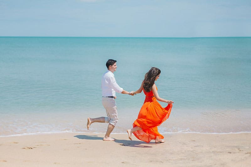 couple walking along the shore with girls orange dress swayed