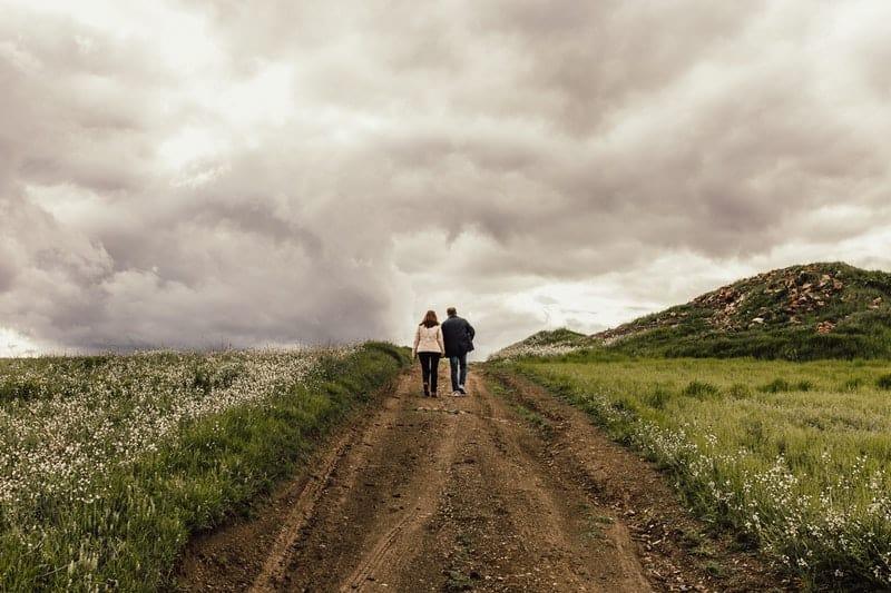couple walking between green fields