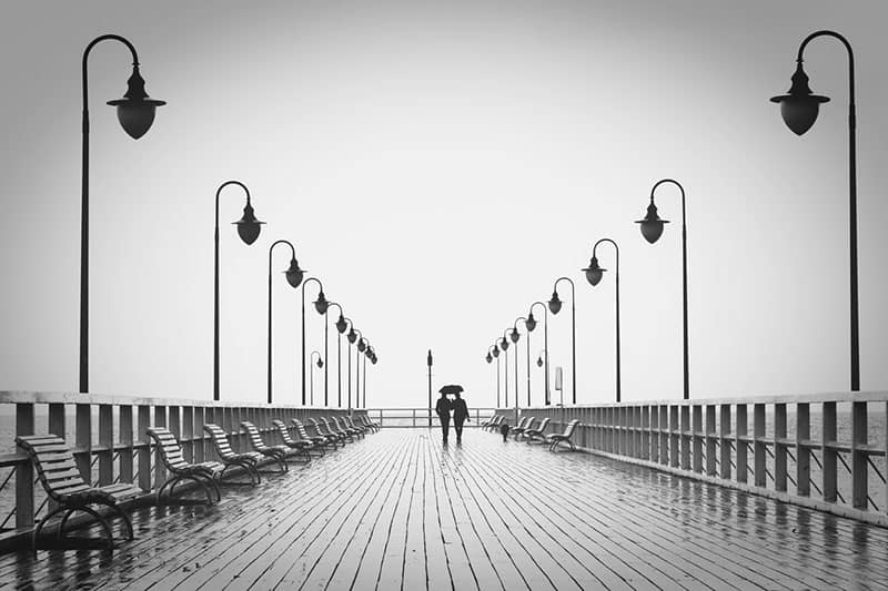 couple walking on boardwalk in black and white