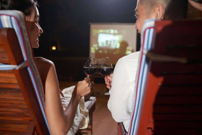 couple watching movie outdoors and cheering glass of wine