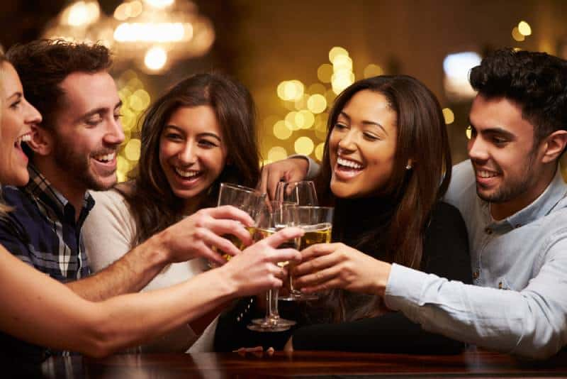 couple with friends cheering at bar