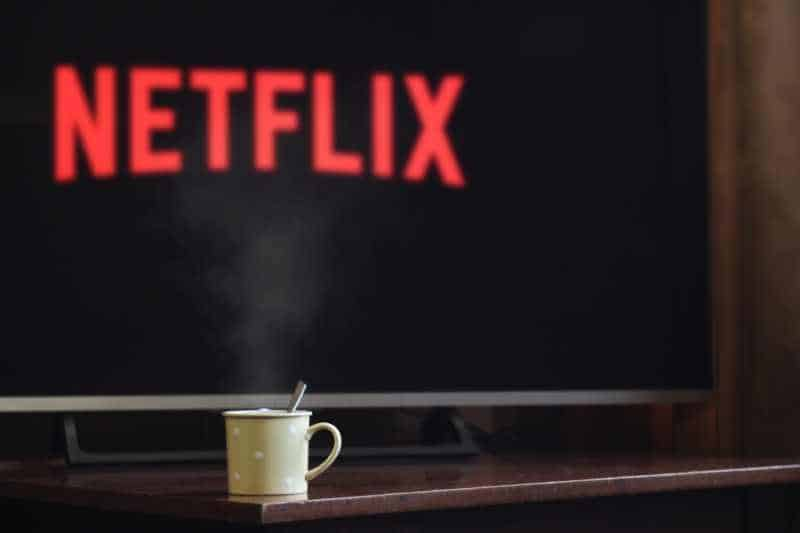Cup near flat screen television with netflix written on the screen