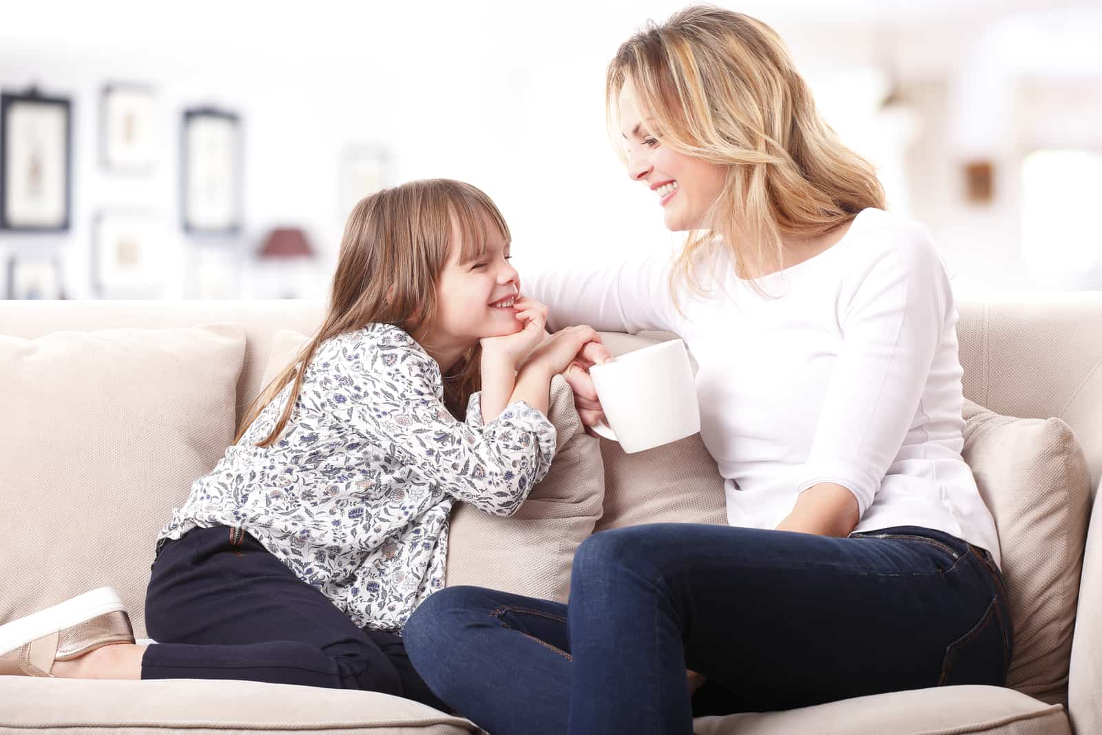daughter and mom sit on the couch and talk