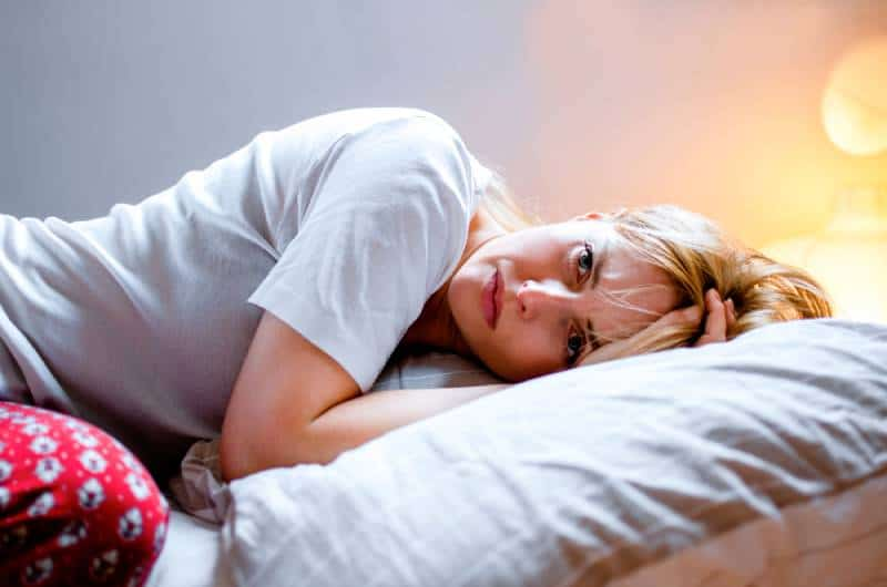 desperate woman lying on bed in pajamas