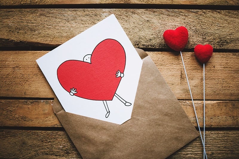 envelope containing a card with a heart embraced by a figure