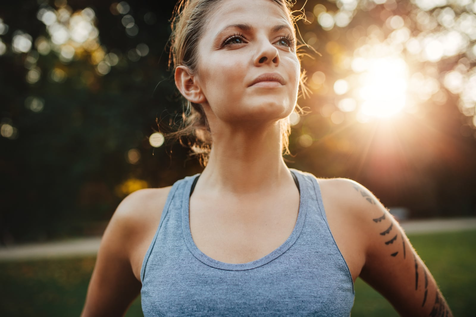 fit young woman in sportswear standing outdoors