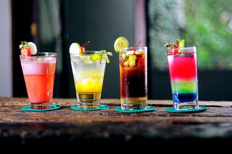 Four glasses with colorfull cocktails on a bar