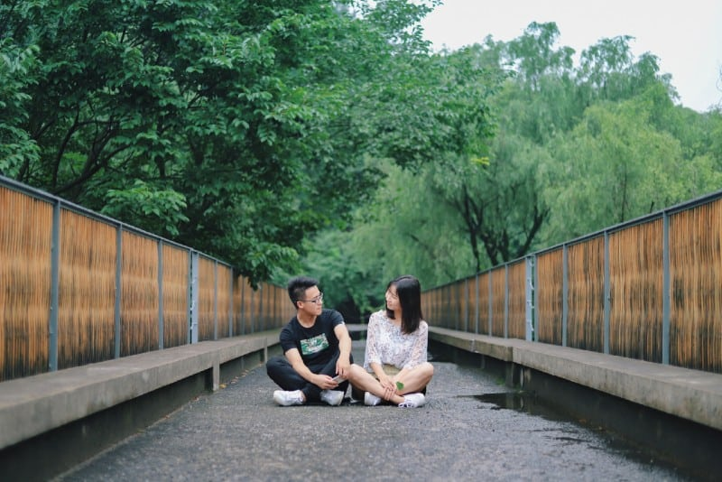 man and woman sitting on floor near trees