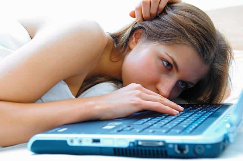 girl lying in bed and typing on laptop