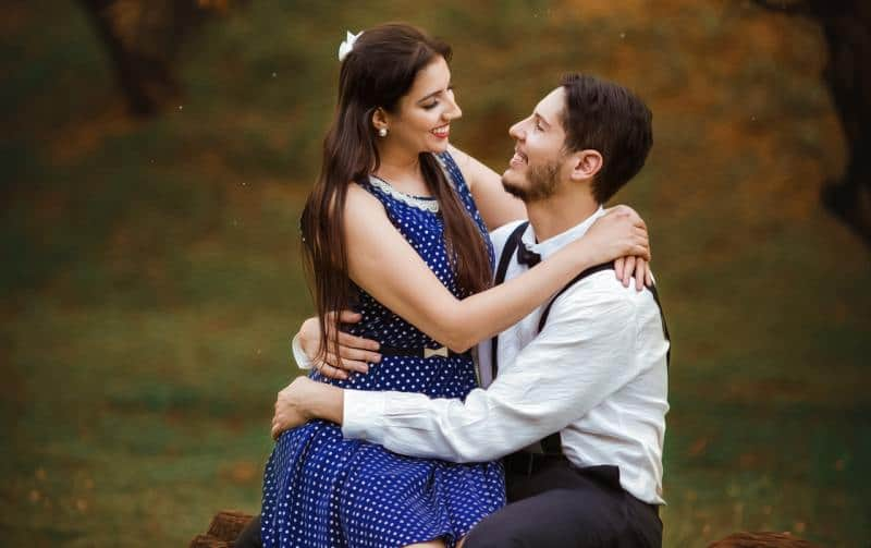 Girl wearing blue dress sitting on mans lap in the forest