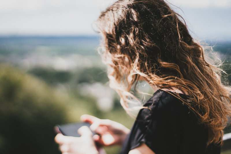 Girl with long hair texting in a blurred natural background