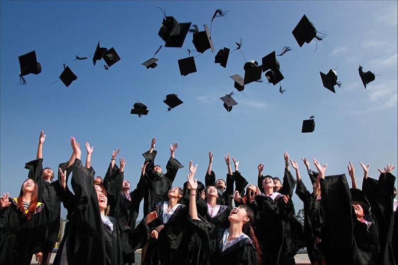 group of graduates throwing graduation caps