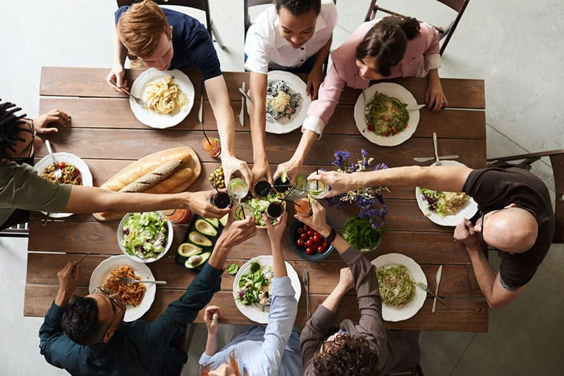 Group of people making toast over dinner table