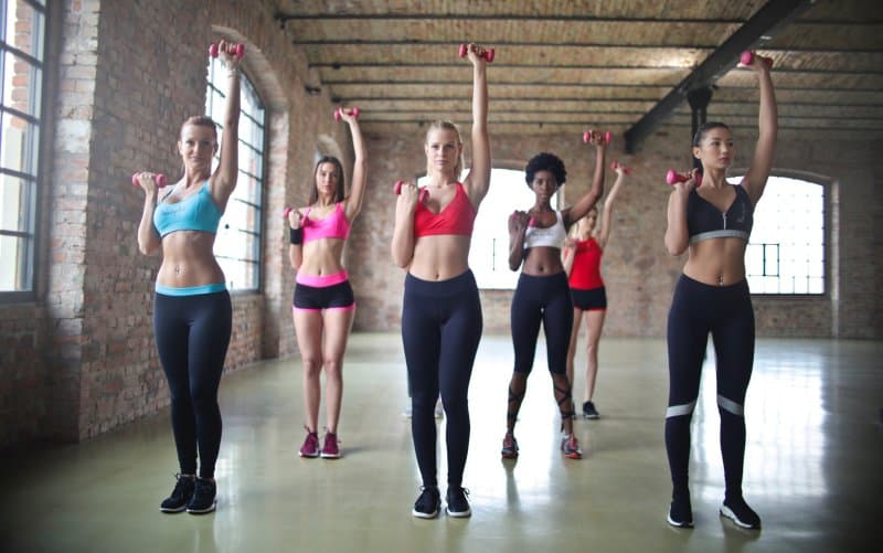 Group of women at the gym exercising using dumbbells