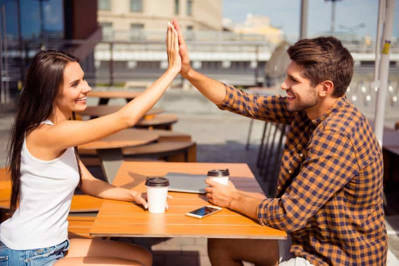 happy couple doing high five at cafe