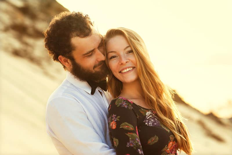 happy couple hugging on beach