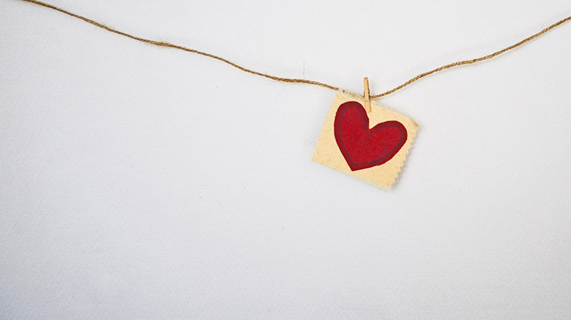 heart-shaped red and beige pendant hanging on string