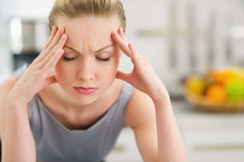houswife with head pain holding her head in kitchen
