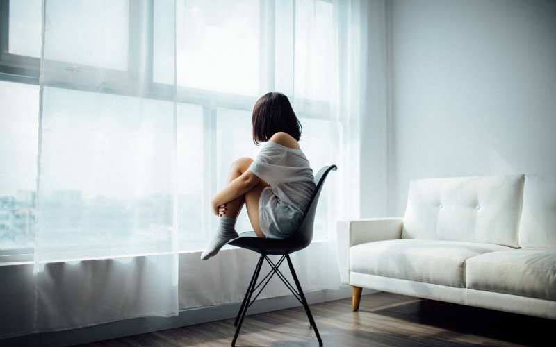 Lonely girl sitting on a chair by the window