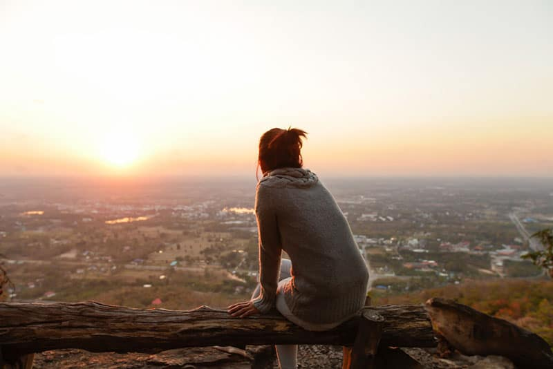 lonely woman sitting in sunset
