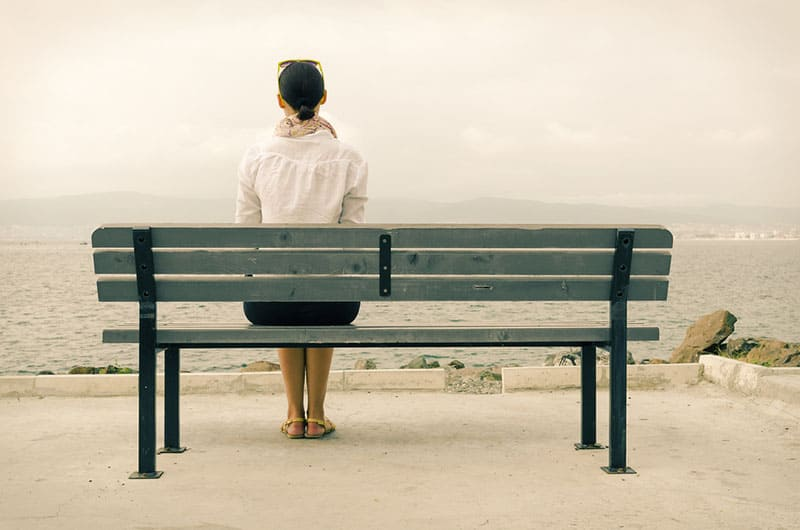lonely woman sitting on bench