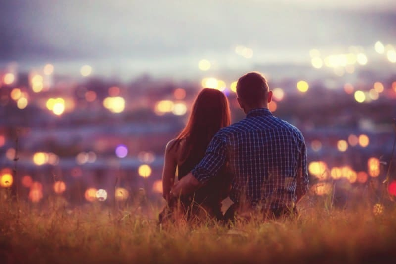 lovely couple watching night city from hill