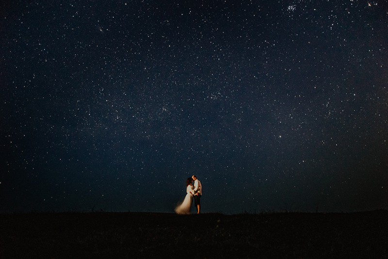 man and woman at night under star sky