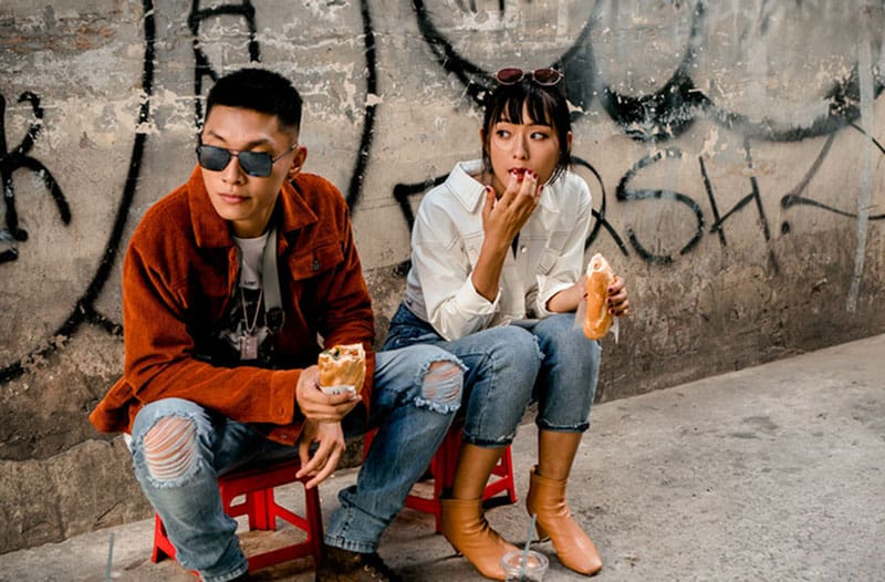 man and woman eating on a sidewalk with vandals on walls sitting on small chairs