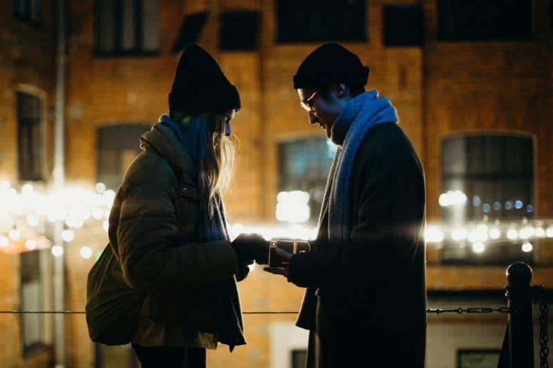 Man and woman facing each other near building in the evening