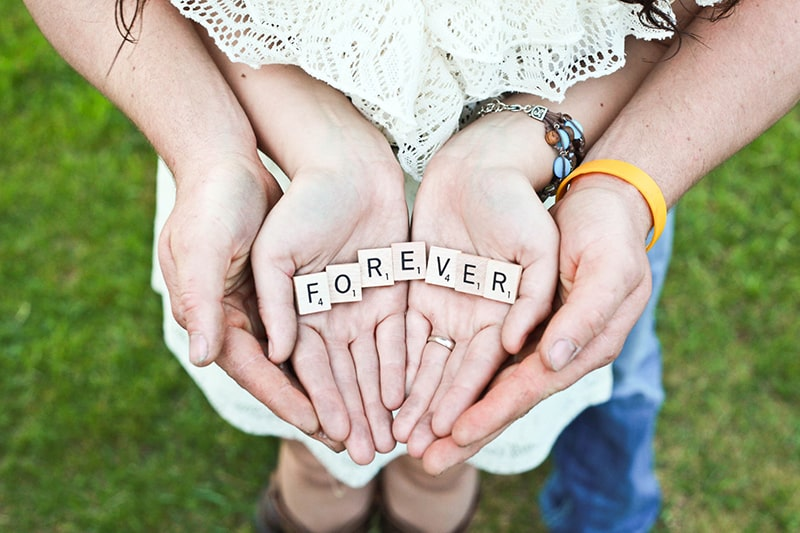 man and woman holding forever scrabble letters while standing on grass