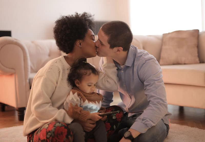 man and woman kissing and kid looking at a gadget