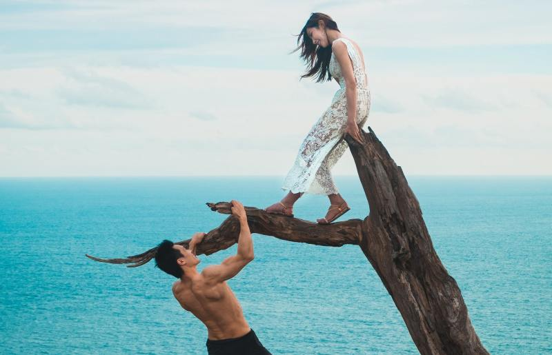 Happy man and woman on a branch by the sea