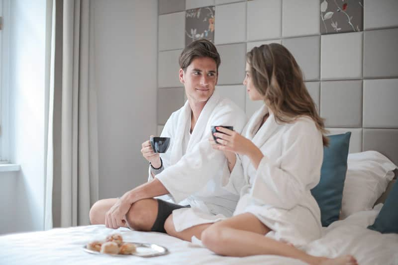 man and woman sitting on bed having breakfast