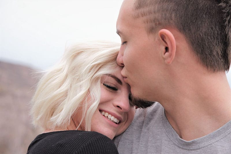 man kissing a woman in forehead