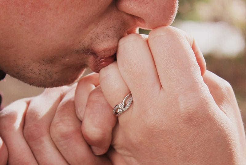 Man kissing wife's hand with wedding ring