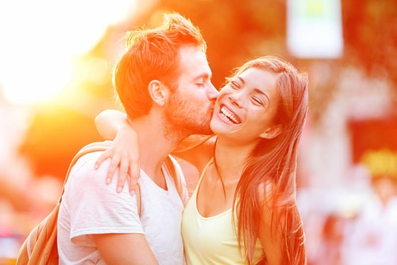 man kissing his smiling girlfriend outside