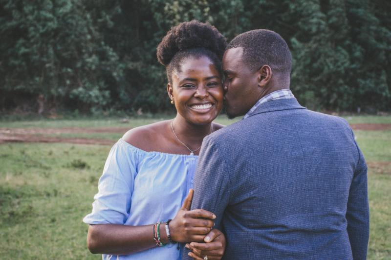 Man kissing left cheek of smiling woman in a nature background