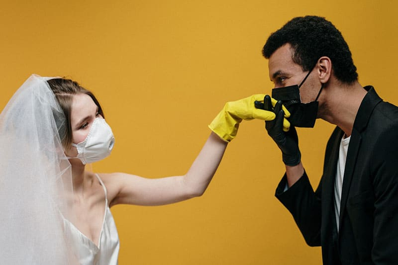 man kissing the hand of a woman with covered mouths