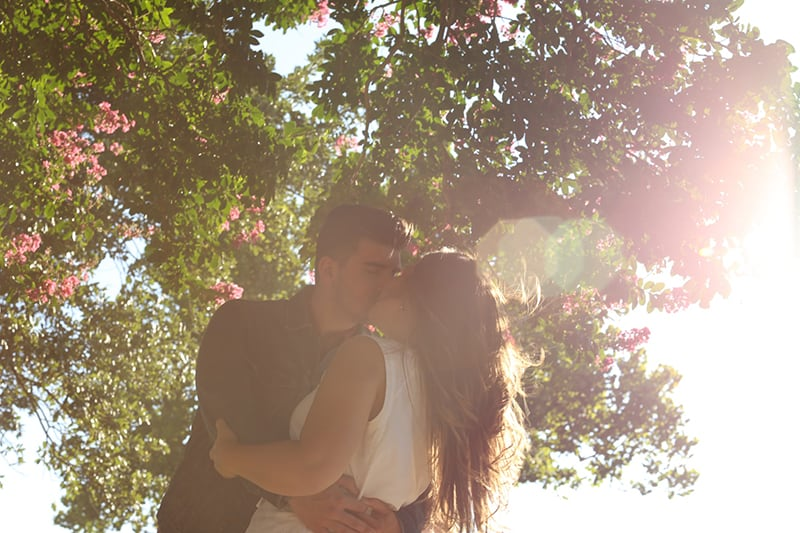 man kissing woman surrounded by trees
