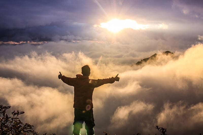 Man at mountain top during sunset arms spread out thumbs up