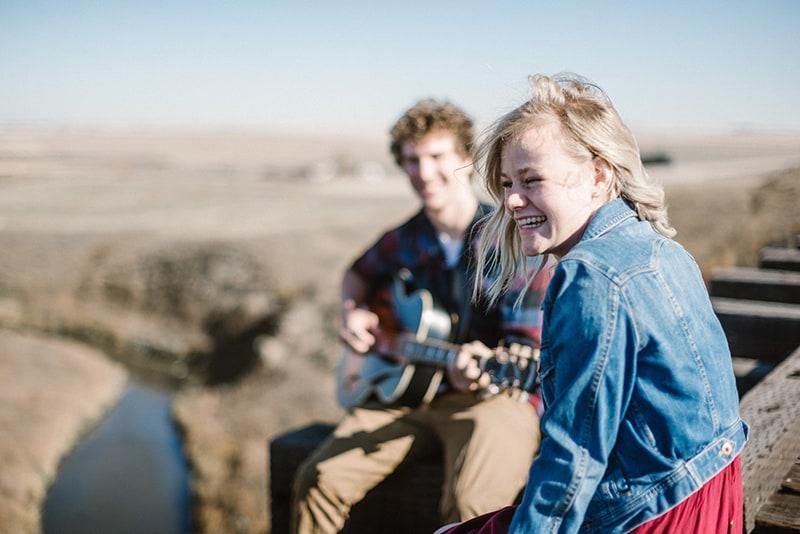 man playing guitar to women on the edge of bridge
