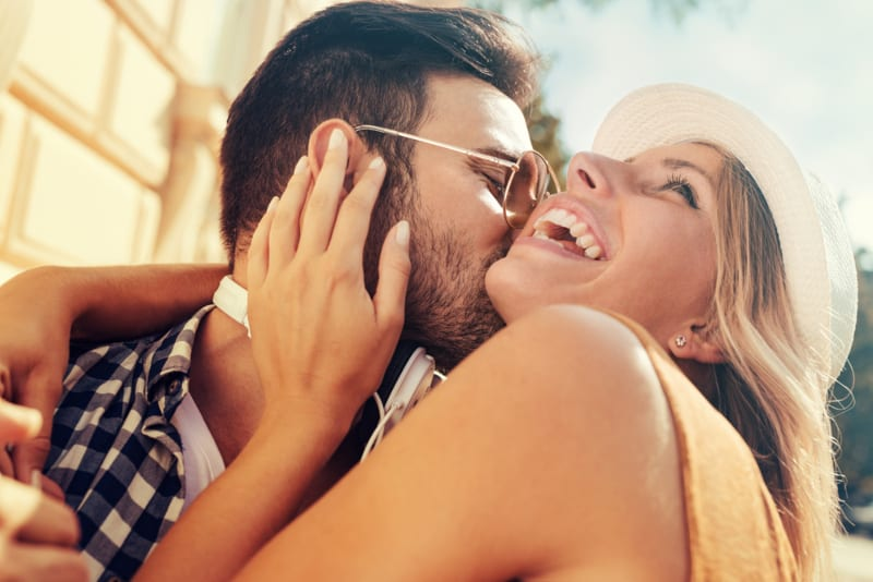 man with sunglasses kissing young blonde