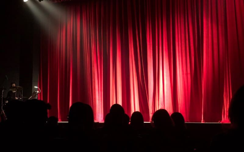 People at theater in front of red stage curtain