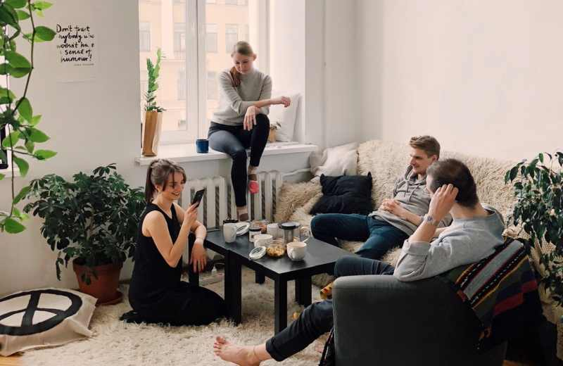 People gathered inside house sitting on sofa and talking to each other
