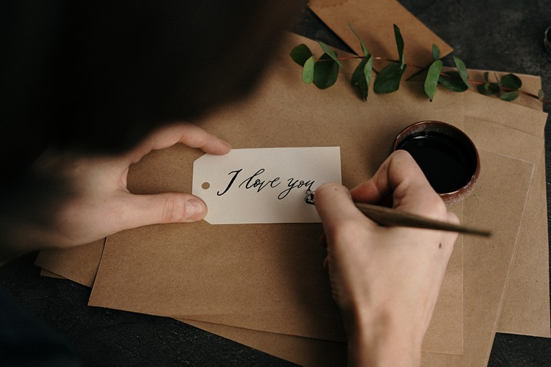 person writing note I love you on white paper