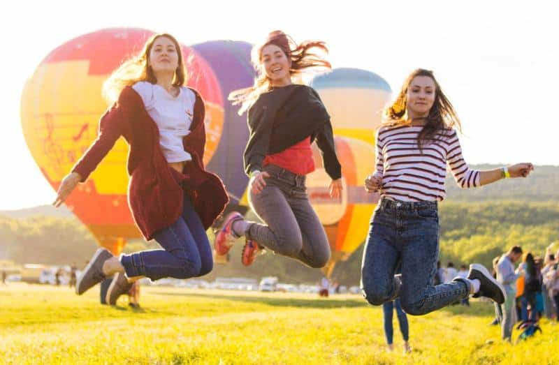 Three young girls jumping on a green field with hot air ballons in the background