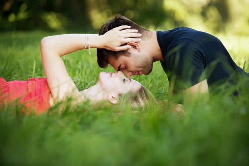 Kissing romnatic couple in nature lying on the grass