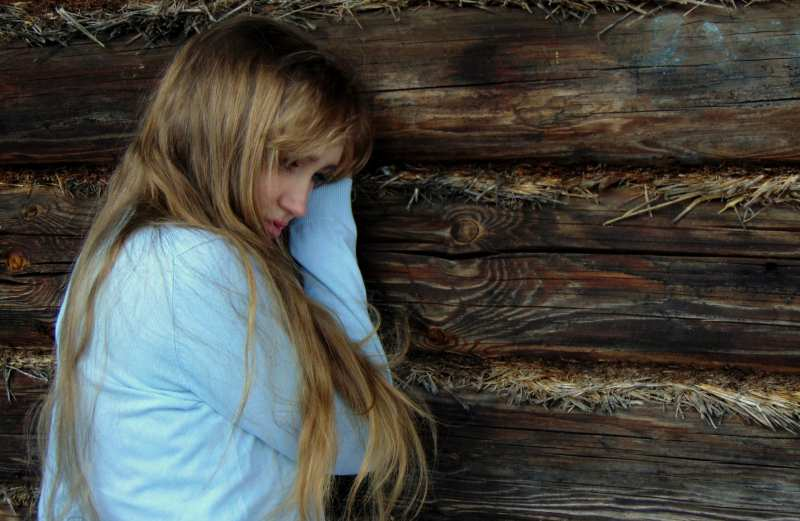 Sad blonde woman with long hair sitting by a woody wall