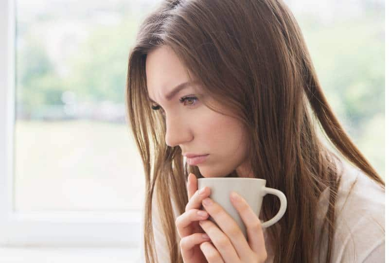 sad woman holding cup and thinking at home