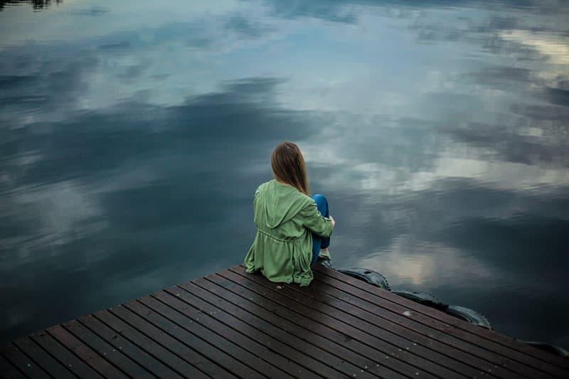 sad woman sitting by the lake